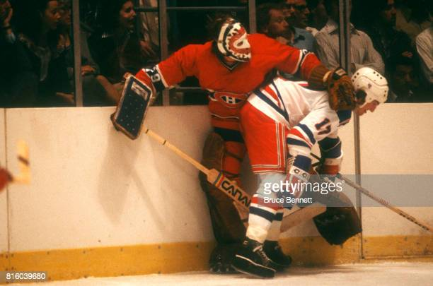 Goalie Ken Dryden of the Montreal Canadiens is checked into the boards by Eddie Johnstone of the New York Rangers during an NHL game circa 1979 at...