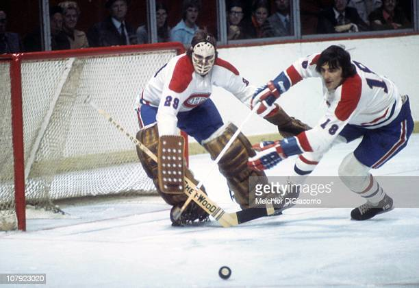 Goalie Ken Dryden of the Montreal Canadiens looks on as teammate Serge Savard looks to skate with the puck circa 1972 at the Montreal Forum in...