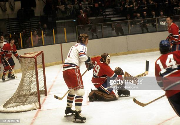 NEW YORK NY DECEMBER 26 Goalie Ken Dryden of the Montreal Canadiens looks to make the save as Vic Hadfield of the New York Rangers looks for a pass...