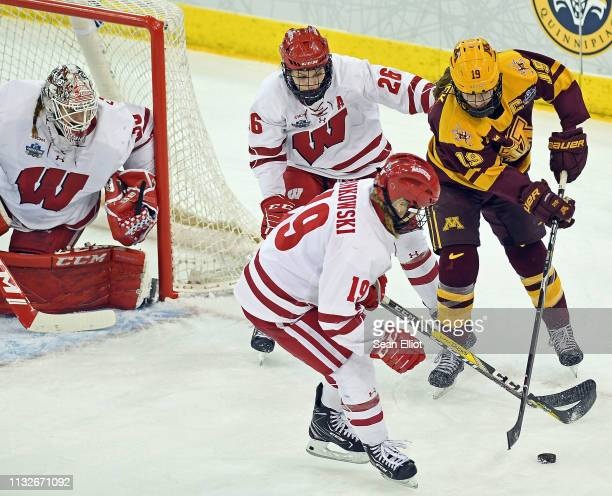 Goalie Kristen Campbell of the Wisconsin Badgers keeps an eye on the puck as teammates Annie Pankowski and Emily Clark defend against center Kelly...