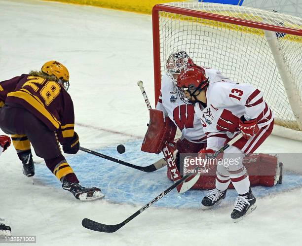 Goalie Kristen Campbell of the Wisconsin Badgers makes a save off a shot from center Tayler Wente of the Minnesota Golden Gophers as Maddie Rolfes of...