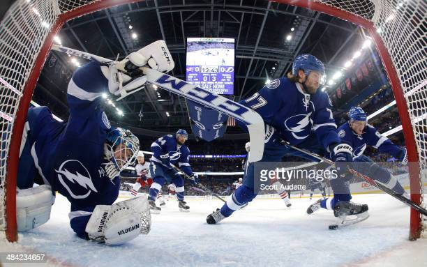 Goalie Kristers Gudlevskis of the Tampa Bay Lightning dives to make a save while Victor Hedman and Andrej Sustr look for the puck against the...