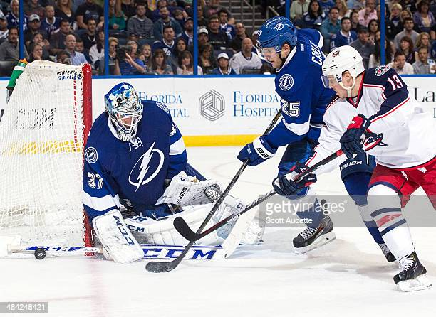 Goalie Kristers Gudlevskis of the Tampa Bay Lightning makes a save while teammates Matt Carle and Cam Atkinson of the Columbus Blue Jackets look for...