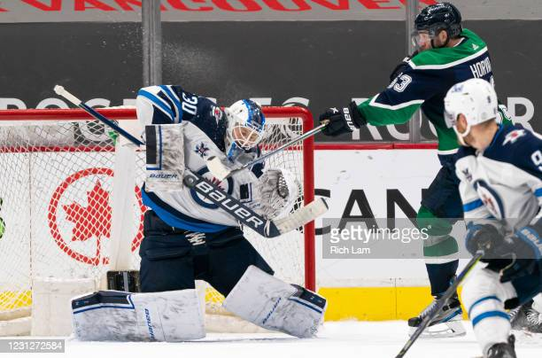 Goalie Laurent Brossoit of the Winnipeg Jets stops a redirected puck off the stick of Bo Horvat of the Vancouver Canucks during NHL hockey action at...