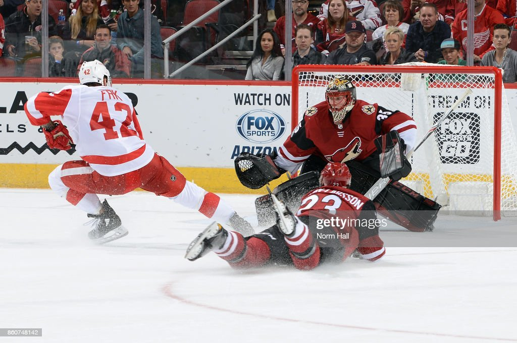 Goalie Louis Domingue #35 of the Arizona Coyotes looks to make a save on the shot by Martin Frk #42 of the Detroit Red Wings as Oliver Ekman-Larsson #23 of the Coyotes defends during the third period at Gila River Arena on October 12, 2017 in Glendale, Arizona.