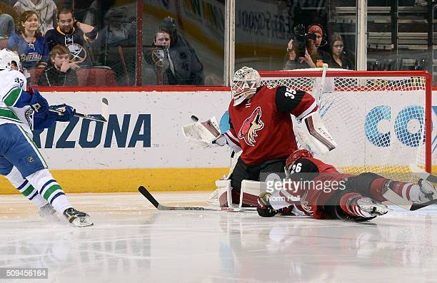 Goalie Louis Domingue of the Arizona Coyotes makes a glove save on the shot by Henrik Sedin of the Vancouver Canucks as Michael Stone of the Coyotes...
