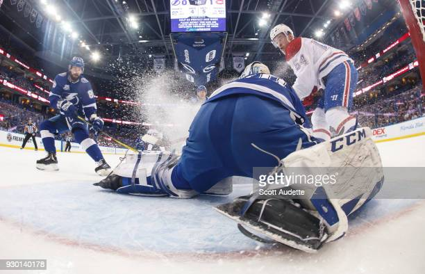 Goalie Louis Domingue of the Tampa Bay Lightning stretches to make a save as teammate Nikita Kucherov and Charles Hudon of the Montreal Canadiens...