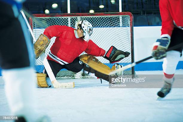 goalie making save in ice hockey game - doelman ijshockeyer stockfoto's en -beelden