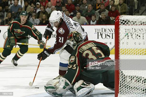 Goalie Manny Fernandez of the Minnesota Wild stops a point blank shot by Peter Forsberg of the Colorado Avalanche during game five of the first round...