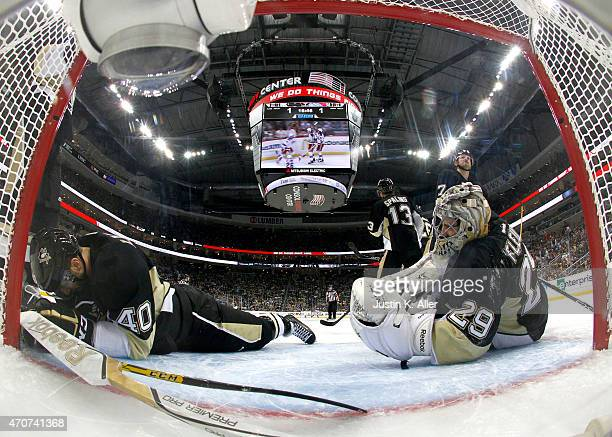 Goalie MarcAndre Fleury and Maxim Lapierre of the Pittsburgh Penguins react after giving up the gamewinning overtime goal to Kevin Hayes of the New...