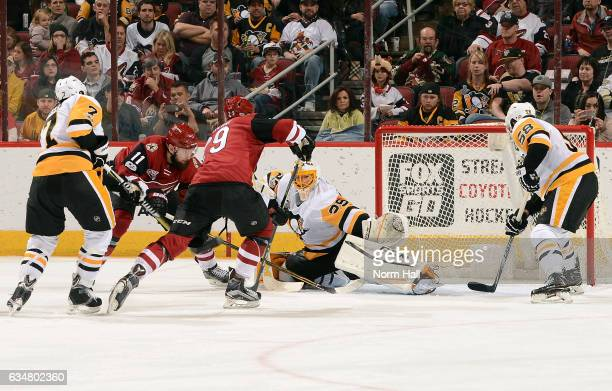 Goalie MarcAndre Fleury of the Pittsburgh Penguins reaches out but can't stop the shot of Martin Hanzal of the Arizona Coyotes as he scores during...