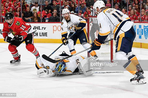 Goalie Marek Mazanec of the Nashville Predators covers the puck in front of Marcus Kruger of the Chicago Blackhawks and Ryan Ellis in the third...