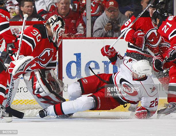 Goalie Martin Brodeur of the New Jersey Devils makes a save as Erik Cole of the Carolina Hurricanes slides into him in the second period of a hockey...