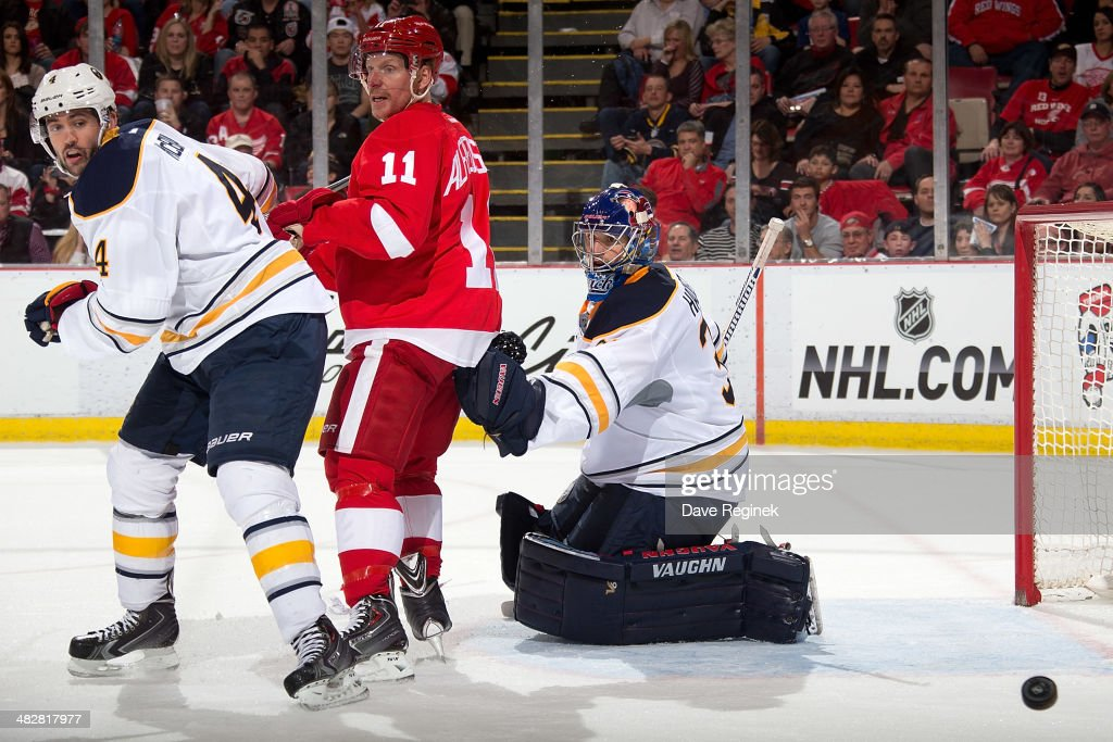 Goalie Matt Hackett #31 of the Buffalo Sabres watches the puck as teammate Jamie McBain #4 battles with Daniel Alfredsson #11 of the Detroit Red Wings in front of the net during an NHL game on April 4, 2014 at Joe Louis Arena in Detroit, Michigan.