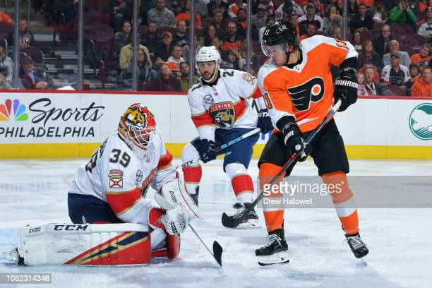 Goalie Michael Hutchinson of the Florida Panthers makes a save on a shot by Travis Konecny of the Philadelphia Flyers as Vincent Trocheck looks on at...