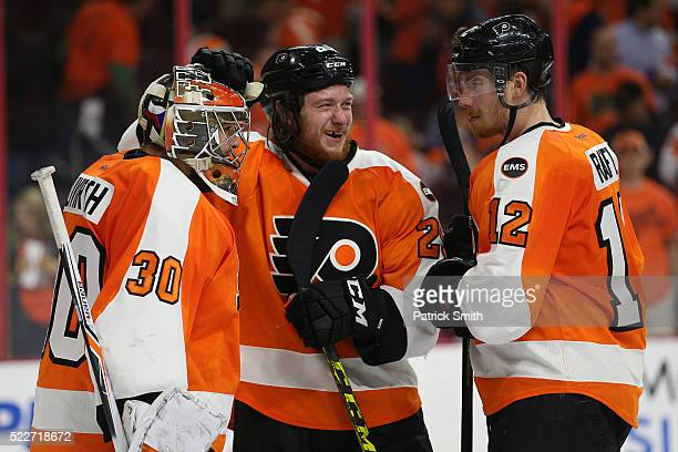Goalie Michal Neuvirth of the Philadelphia Flyers celebrates with teammates Ryan White and Michael Raffl after defeating the Washington Capitals in...