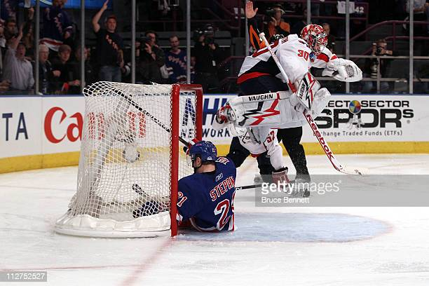 Goalie Michal Neuvirth of the Washington Capitals jumps over Derek Stepan of the New York Rangers as Stepan slides into the net in Game Four of the...
