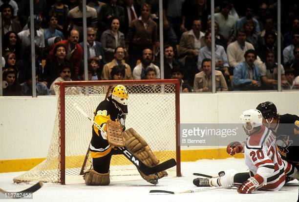 Goalie Michel Dion of the Pittsburgh Penguins looks to make the save on Hector Marini of the New Jersey Devils on October 5 1982 at the Brendan Byrne...