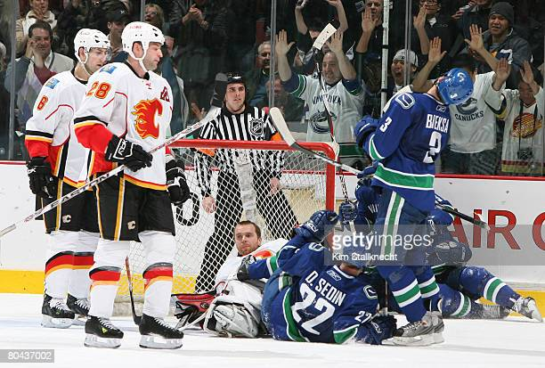 Goalie Miikka Kiprusoff of the Calgary Flames loses his helmet as Markus Naslund of the Vancouver Canucks scores making the game 22 at the end of the...