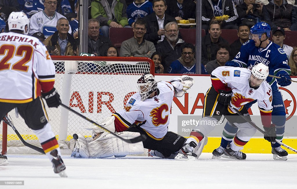 Goalie Miikka Kiprusoff #34 of the Calgary Flames makes a toe save while Mark Giordano #5 and Henrik Sedin #33 of the Vancouver Canucks battle at the side of the net during the first period of NHL action on January 23, 2013 at Rogers Arena in Vancouver, British Columbia, Canada. Lee Stempniak #22 of the Calgary Flames looks on during the play.