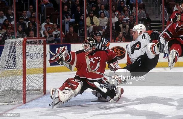 Goalie Mike Dunham of the New Jersey Devils looks to make the save as Rod Brind'Amour of the Philadelphia Flyers flies through the air on April 13...