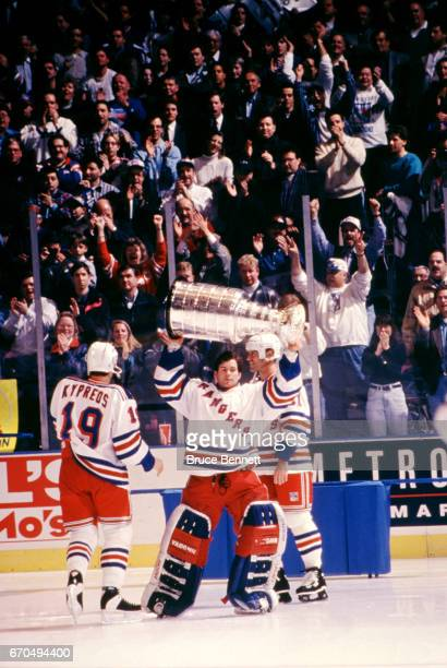 Goalie Mike Richter of the New York Rangers skates on the ice with the Stanley Cup Trophy as Mark Messier and Nick Kypreos talk after the Rangers...