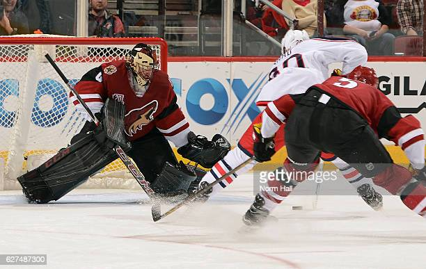 Goalie Mike Smith of the Arizona Coyotes positions himself for a save as Brandon Saad of the Columbus Blue Jackets skates in with the puck while...