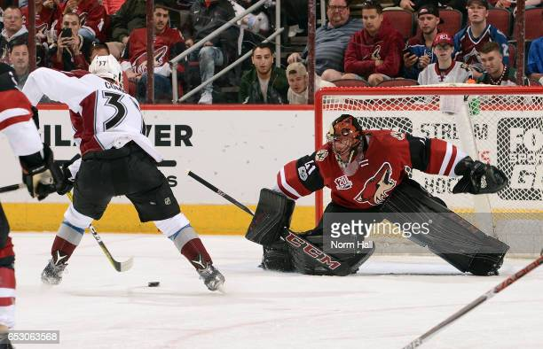Goalie Mike Smith of the Arizona Coyotes positions himself for a save as JT Compher of the Colorado Avalanche skates in with the puck during the...