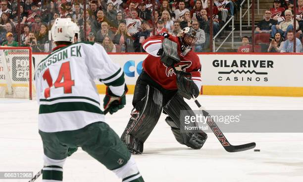 Goalie Mike Smith of the Arizona Coyotes skates out to clear the puck in front of Joel Eriksson Ek of the Minnesota Wild during the first period at...