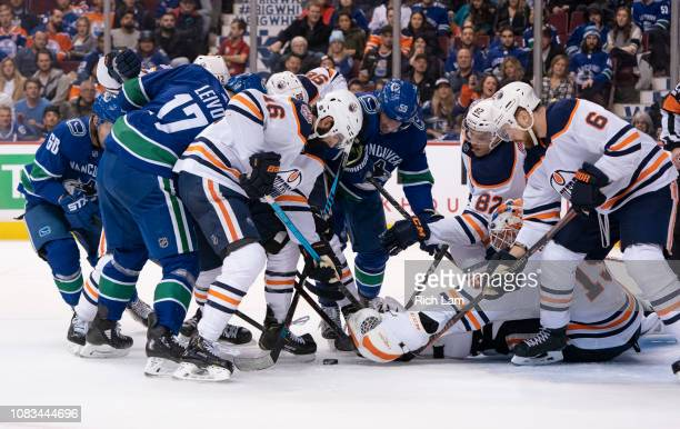 Goalie Mikko Koskinen of the Edmonton Oilers reaches to to try and cover up the puck while Jujhar Khaira Jesse Puljujarvi Caleb Jones and Adam...