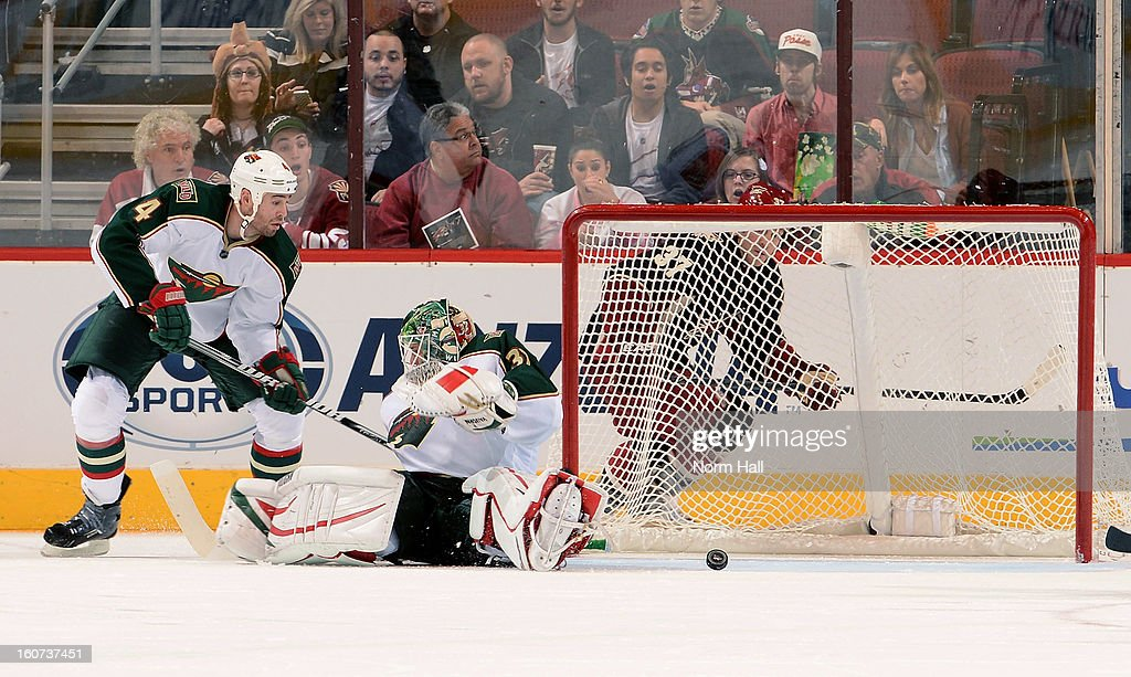 Goalie Niklas Backstrom #32 and defenseman Clayton Stoner #4 of the Minnesota Wild watch the puck roll across the face of the goal as Raffi Torres #37 of the Phoenix Coyotes skates behing the net during the third period at Jobing.com Arena on February 4, 2013 in Glendale, Arizona.