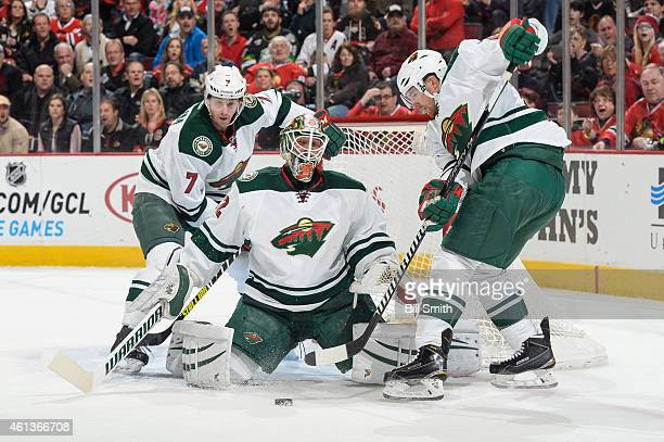 Goalie Niklas Backstrom of the Minnesota Wild gets in position to stop the puck as Jonathon Blum stands behind during the NHL game at the United...