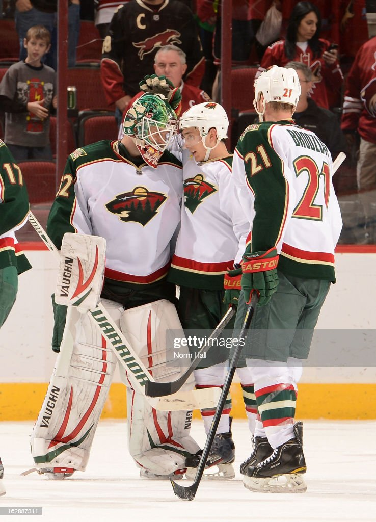 Goalie Niklas Backstrom #32 of the Minnesota Wild is congratulated by teammates Jared Sturgeon #46 and Kyle Brodziak #21 after a 4-3 victory over the Phoenix Coyotes at Jobing.com Arena on February 28, 2013 in Glendale, Arizona.