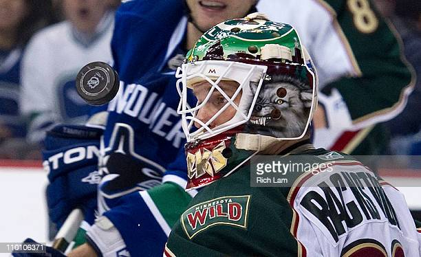 Goalie Niklas Backstrom of the Minnesota Wild keeps an eye on the airborne puck after making a save against the Vancouver Canucks during the second...