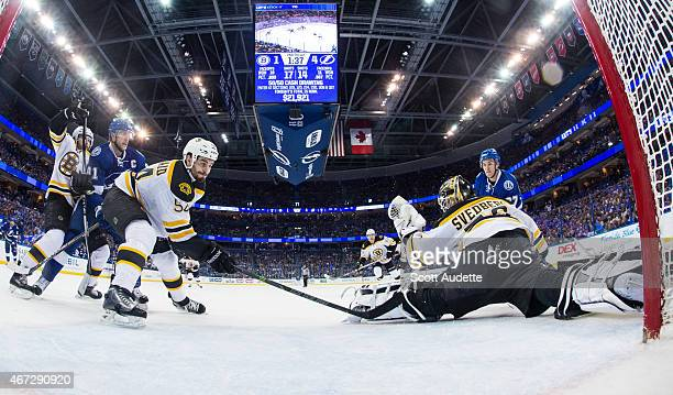 Goalie Niklas Svedberg the Boston Bruins makes a glove save during the second period while teammate Adam McQuaid as well as Steven Stamkos and...