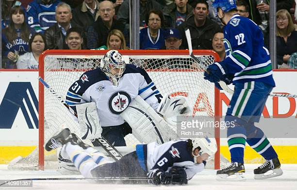 Goalie Ondrej Pavelec of the Winnipeg Jets makes a glove save as Ron Hainsey sprawls to try and block the shot and Daniel Sedin of the Vancouver...