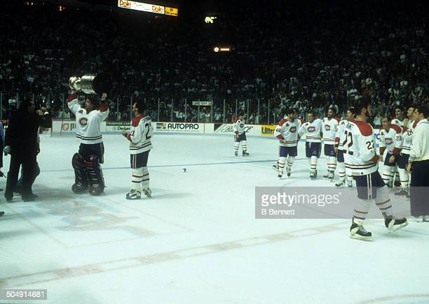 Goalie Patrick Roy of the Montreal Canadiens celebrates with the Stanley Cup as teammate Guy Carbonneau looks on after Game 5 of the 1993 Stanley Cup...