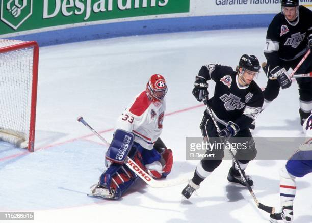 Goalie Patrick Roy of the Montreal Canadiens looks to make the save as Luc Robitaille of the Los Angeles Kings tries to set a screen during Game 1 of...