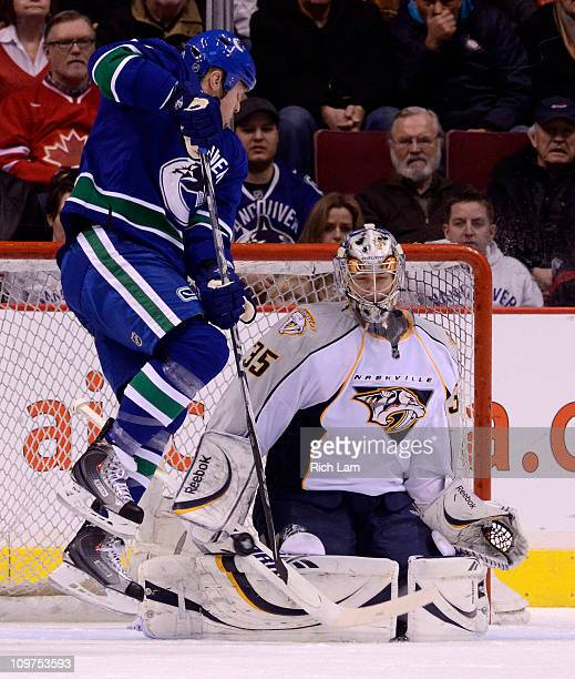 Goalie Pekka Rinne of the Nashville Predators makes a pad save while Raffi Torres of the Vancouver Canucks jumps out of the way during the first...