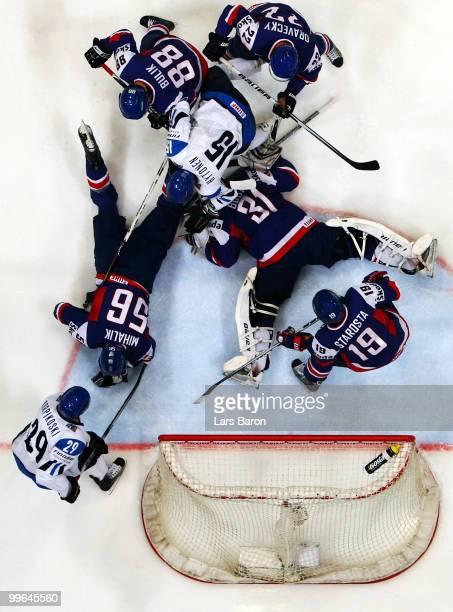 Goalie Peter Budaj of Slovakia lies on the ice under Juha Pekka Hytonen of Finland during the IIHF World Championship qualification round match...
