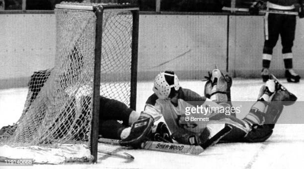 Goalie Rejean Lemelin of the Atlanta Flames is tripped up by Nick Libett of the Detroit Red Wings during their game on January 28 1979 at the Omni...