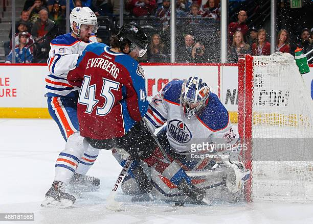 Goalie Richard Bachman of the Edmonton Oilers looks to control the puck as Dennis Everberg of the Colorado Avalanche and Justin Schultz of the...