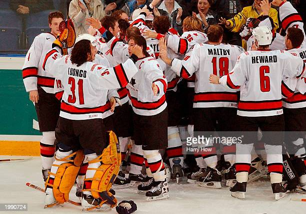 Goalie Roberto Luongo of Canada celebrates with Ryan Smyth after an overtime goal by Anson Carter#22 of Canada for a 3-2 win over Sweden in the Gold...