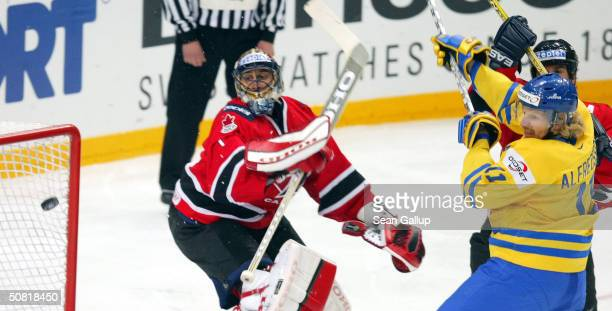 Goalie Roberto Luongo of Canada deflects the puck from Daniel Alfredsson of Sweden in the teams' match at the International Ice Hockey Federation...