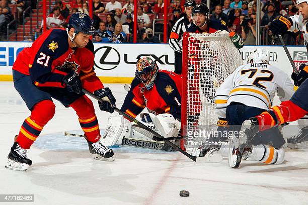 Goalie Roberto Luongo of the Florida Panthers defends the net with the help of teammate Krys Barch against Luke Adam of the Buffalo Sabres at the BBT...