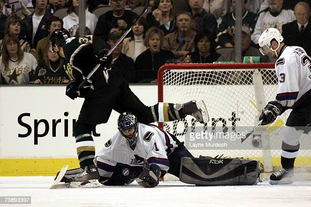 Goalie Roberto Luongo of the Vancouver Canucks covers the puck as Joel Lundqvist of the Dallas Stars leaps over him during the first overtime of game...