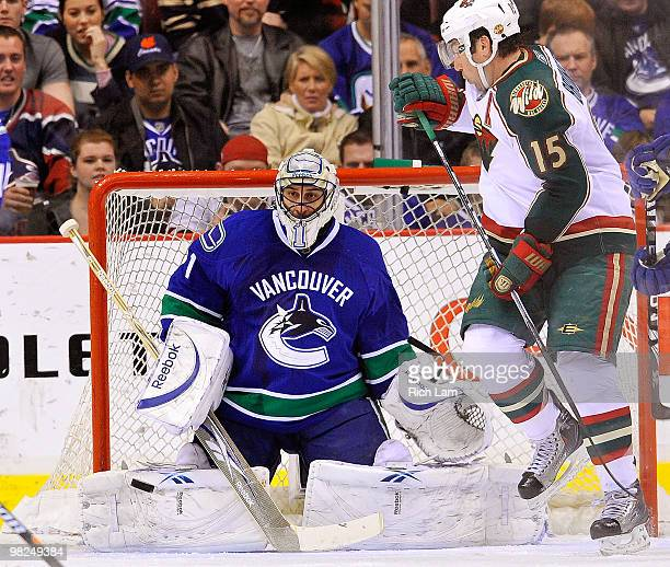Goalie Roberto Luongo of the Vancouver Canucks gets into position to make a save with Andrew Brunette of the Minnesota Wild in close looking for a...