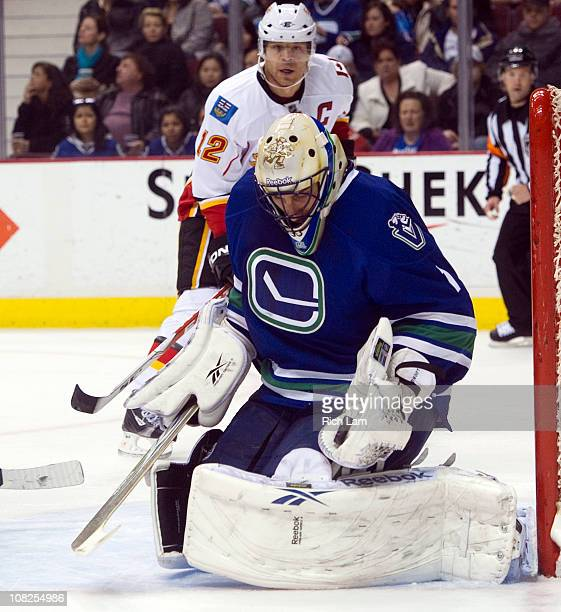 Goalie Roberto Luongo of the Vancouver Canucks makes a glove save while Jarome Iginla of the Calgary Flames looks on during the first period in NHL...