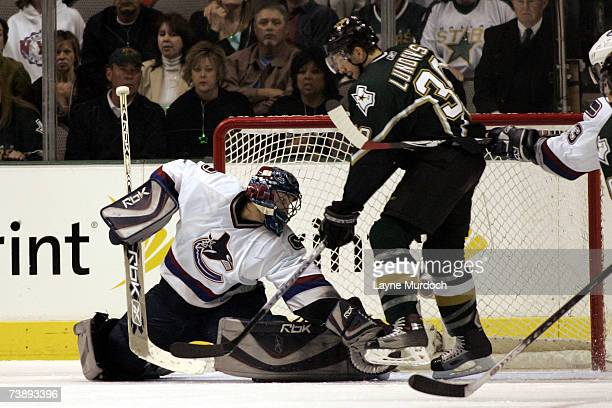 Goalie Roberto Luongo of the Vancouver Canucks reaches for the puck as Joel Lundqvist of the Dallas Stars looks for a rebound during the first...