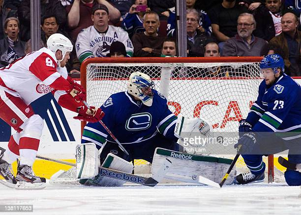 Goalie Roberto Luongo of the Vancouver Canucks slides across his crease to make a save as Johan Franzen of the Detroit Red Wings and Alexander Edler...